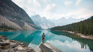 Woman admiring mountains and lake.