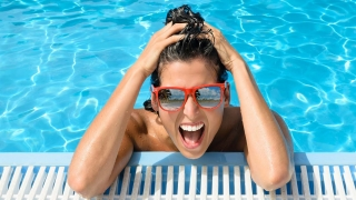 Happy woman in swimming pool wearing sunglasses.