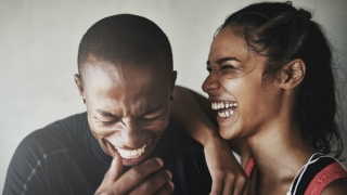 Cute couple laughing hard together.