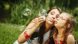 Happy mom and daughter blowing bubbles outside.