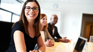 Smiling woman with colleagues in an office.