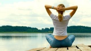 Woman meditating by a lake.