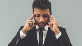 businessman in classic suit is touching his temples while concentrating, on gray background