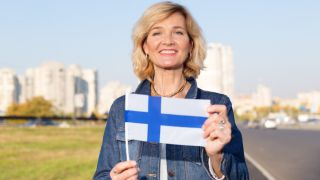 Happy mature woman with flag of Finland standing against the background of a city street and blue sky.