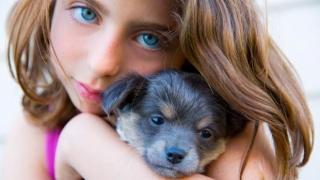 Girl hugging her puppy