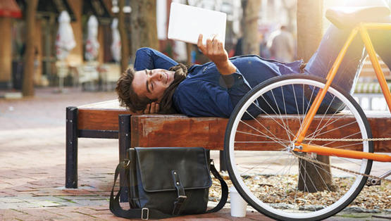 Person reading tablet outside.