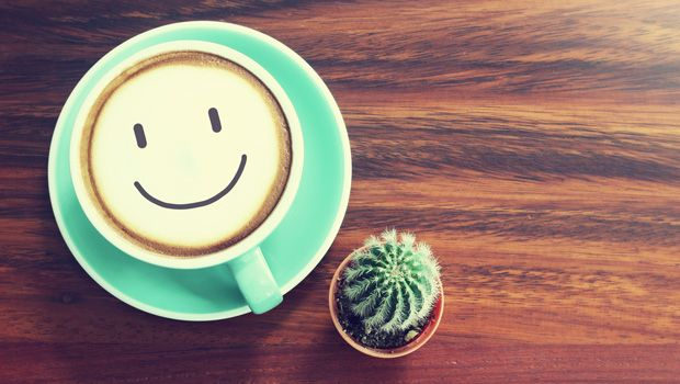 Coffee cup & Cactus on wooden background with vintage filter