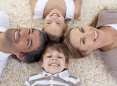 Family lying on floor with their heads touching